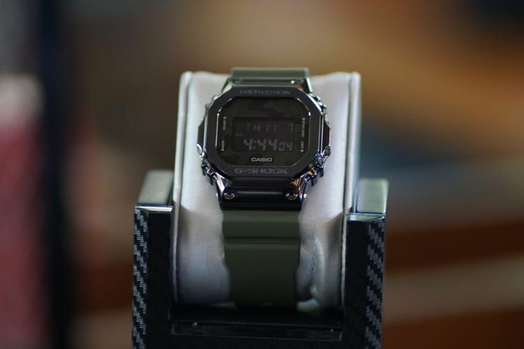 Jam tangan G-Shock GM-5600B-3DR dengan bezel hitam black ion-plated steel yang dipadukan dengan warna hijau militer, lengkap dengan motif kamuflase-nya.