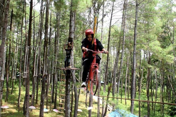 Seorang pengunjung mencoba menggunakan waha sepeda melayang di Wisata Hutan Pinus Samparona, Kelurahan Kaisabu Baru, Kecamatan Sorawolio, Kota Baubau, Sulawesi Tenggara, Minggu (11/2/2018).