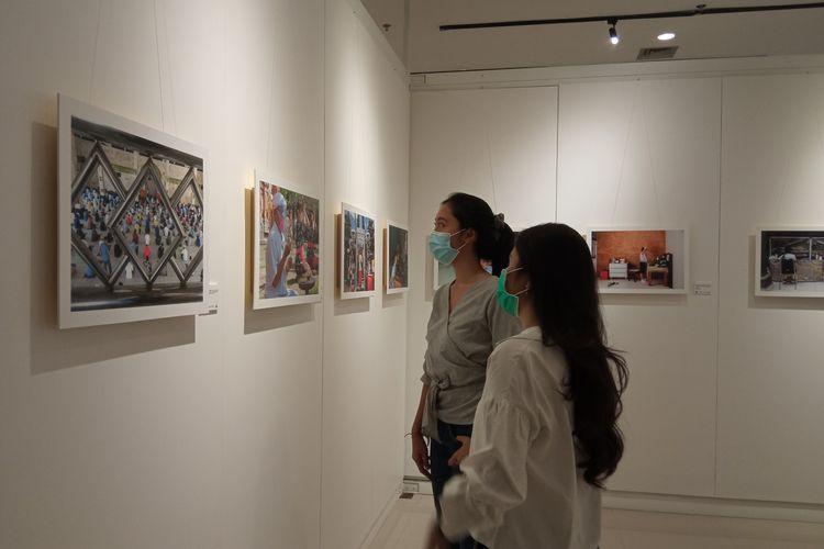 Pengunjung melihat sebuah foto yang ditampilkan dalam pameran foto Grubug Agung