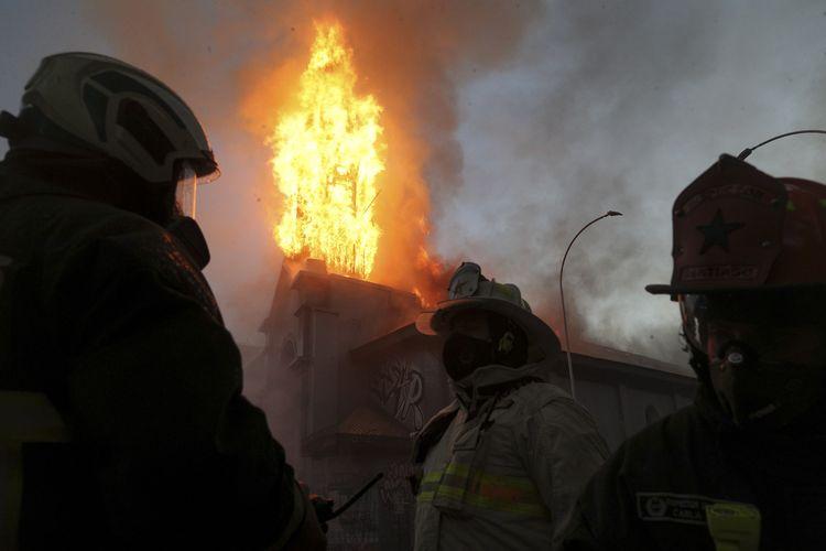 Tim pemadam kebakaran berusha menjinakkan api di Gereja Parroquia de La Asuncion yang dibakar dalam unjuk rasa di Santiago, Chile, pada 18 Oktober 2020.
