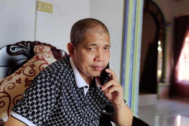 Khairuddin Siregar (51) saat menerima telepon dari orang yang mengaku mau membantu mencari istrinya yang hilang, Ervina Lubis (40), di Desa Tanjung Sawit, Kecamatan Tapung, Kabupaten Kampar, Riau, Selasa (15/6/2021).