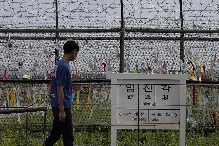 Seorang pengunjung berjalan di depan tanda arah yang menunjukkan jarak ke kota Kaesong Korea Utara dan ibuvkota Korea Selatan, Seoul di dekat pagar kawat yang dihiasi dengan pita yang ditulis dengan pesan yang memuat keinginan penyatuan kembali kedua Korea di Paviliun Imjingak di Paju, Korea Selatan, Minggu, 14 Juni 2020.