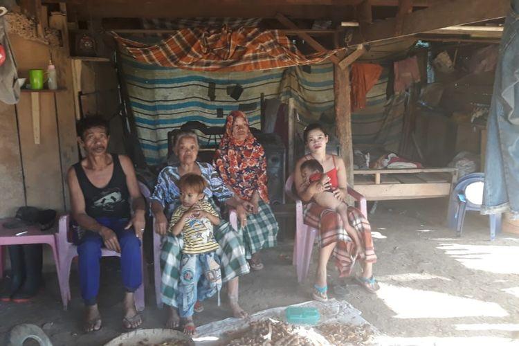 Bakri dan keluarganya di bawa kolom rumah, Desa Bululohe,  Kabupaten Bulukumba, Sulawesi Selatan.