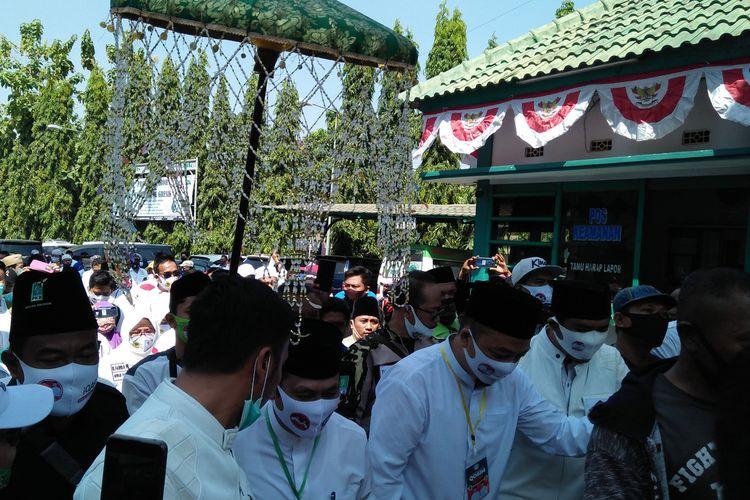 Pasangan Mohammad Qosim-Asluchul Alif berjalan kaki dari Masjid Agung menuju kantor KPU Gresik, Minggu (6/9/2020).