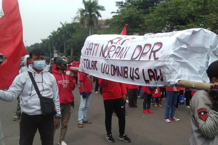 Masa membawa keranda saat gelar aksi tolak omnibus law Undang-Undang Cipta Kerja di kawasan Patung Kuda, Jakarta Pusat (16/10/2020)