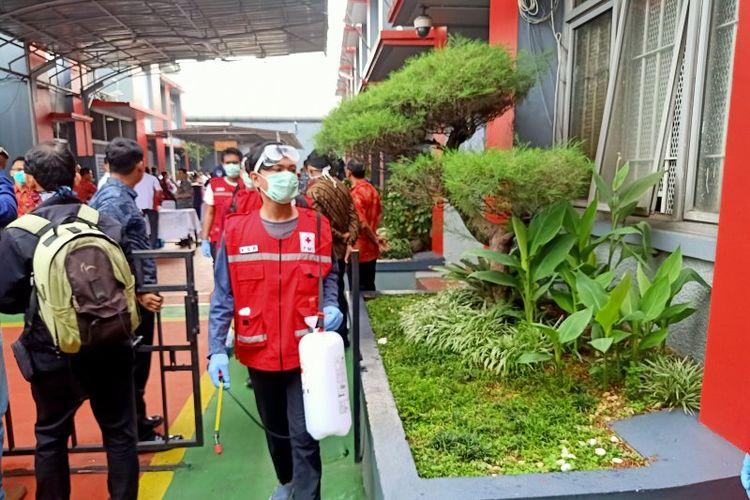 Relawan Palang Merah Indonesia (PMI) memasuki gerbang Lapas Klas 1 Cipinang, Jakarta Timur, untuk melakukan penyemprotan disinfektan guna mencegah wabah COVID-19, Minggu (21/3/2020).