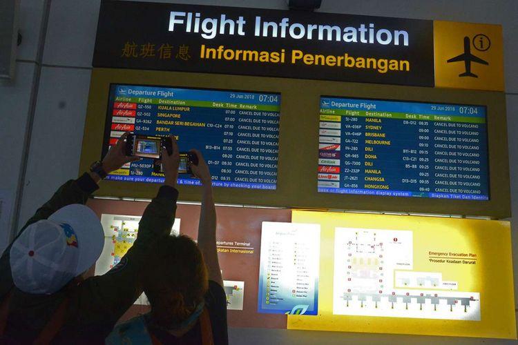 Sejumlah penumpang mencari informasi jadwal penerbangan melalui layar monitor di Bandara Ngurah Rai, Bali, Jumat (29/6/2018). PT Angkasa Pura I menutup sementara operasional Bandara Internasional I Gusti Ngurah Rai selama 16 jam mulai pukul 03.00 WITA hingga 19.00 WITA setelah Direktorat Jenderal Perhubungan Udara mengeluarkan NOTAM A2551/18 pada Jumat ini akibat dampak sebaran abu vulkanik Gunung Agung.