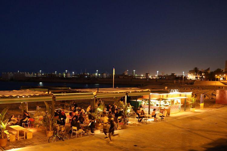 Orang-orang memadati kafe teras Chiringuito (bar pantai) di pantai Barceloneta, untuk merayakan pencabutan lockdown fase satu, di Barcelona, Spanyol, 25 Mei 2020.