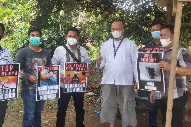 Lima orang anggota intelijen Polda Lampung menunjukkan poster yang digunakan warga berinisial Rnuntuk memprotes Jokowi. Foto ini beredar dengan narasi bahwa anggota itu yang berdemonstrasi.