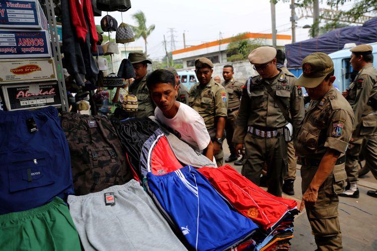 Petugas Satpol PP melakukan penertiban kepada pedagang kaki lima yang berjualan di kawasan Pasar Tanah Abang, Jakarta, Rabu (17/5/2017). Penertiban dilakukan setiap hari menyusul mulai banyaknya PKL yang berjualan di trotoar dan jalan kawasan Pasar Tanah Abang.