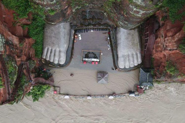 Banjir mengancam kaki Buddha di foto ini dari 12 Agustus.