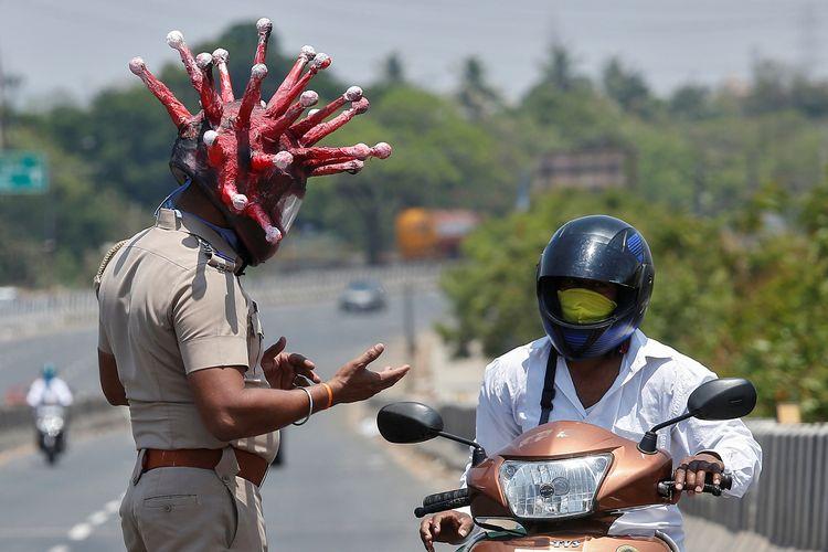 Inspektur Polisi Rajesh Babu, sembari mengenakan virus corona, memperingatkan warga yang masih keluar rumah di tengah lockdown pada 28 Maret 2020 di Chennai.