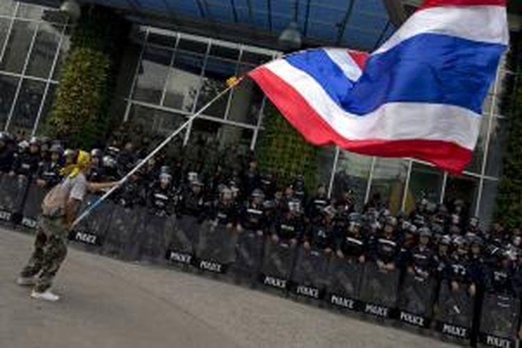 Seorang pengunjuk rasa anti-pemerintah mengibarkan bendera Thailand di depan barikade polisi yang menjaga sebuah stasiun televisi di Bangkok, Jumat (9/5/2014).