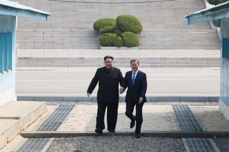 Pemimpin Korea Utara Kim Jong Un (kiri) melangkah bersama Presiden Korea Selatan Moon Jae-in (kanan) melintasi Garis Demarkasi Militer yang membagi negara mereka, menjelang pertemuan di Gedung Perdamaian resmi di Panmunjom, Jumat (27/4/2018).