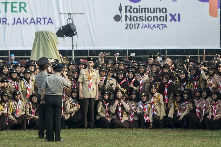 Presiden Joko Widodo (tengah) berfoto bersama para anggota pramuka dalam acara Raimuna Nasional XI yang bertepatan dengan peringatan ulang tahun Pramuka ke-56 di, Bumi Perkemahan Cibubur, Jakarta, Senin (14/8/2017). Sebanyak 15 ribu Pramuka Penegak dan Pandega dari 34 provinsi dan 514 kota/kabupaten serta pramuka luar negeri mengikuti kegiatan bertajuk Pramuka untuk Masa Depan Indonesia: kreatif, inovatif, berkarakter. ANTARA FOTO/Rosa Panggabean/aww/17.