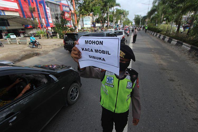Polisi memeriksa kendaraan bermotor saat hari pertama Pembatasan Sosial Berskala Besar (PSBB) di perbatasan Kota Banjarmasin, Kalimantan Selatan, Jumat (24/4/2020). Pemerintah Kota Banjarmasin resmi menerapkan PSBB dalam rangka percepatan penangan COVID-19 selama 14 hari dimulai 24 April hingga 7 Mei 2020.