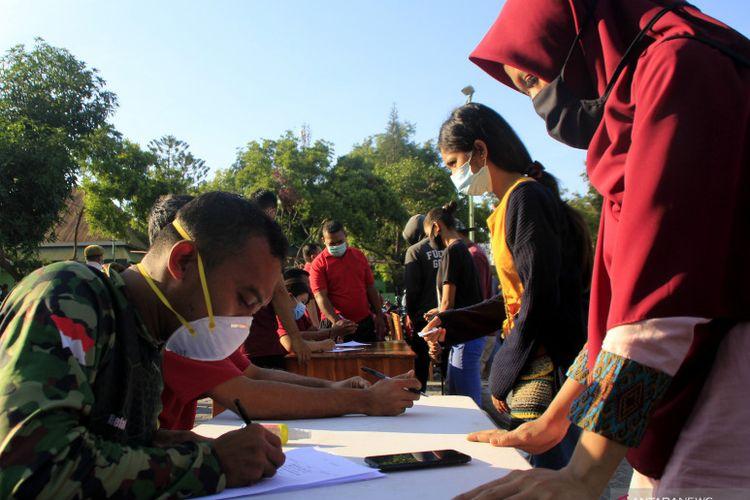 Petugas kesehatan dari RST Wirasakti Kupang mengisi biodata warga yang mengantre untuk mendaftar terima suntikan vaksin Covid-19 di RST Wirasakti Kota Kupang, NTT, Senin (12/7/2021).