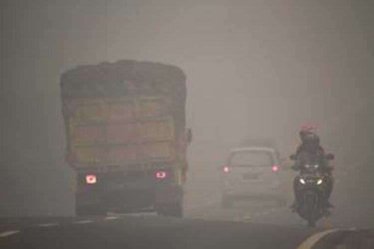 Suasana kabut asap sebelum memasuki kota Sampit (26/10/2015). Kabut asap menyelimuti sepanjang jalan Trans Kalimantan dari Pontianak hingga Palangkaraya.