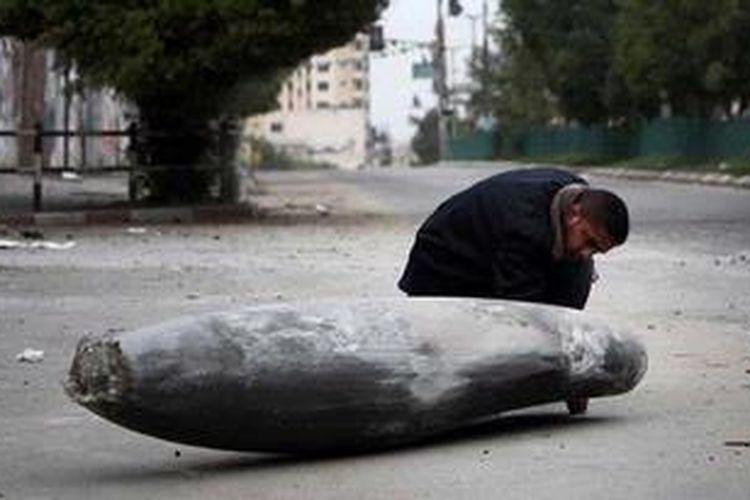 Seorang polisi Palestina mengamati sebuah bom Israel yang jatuh namun tidak meledak di salah satu ruas jalan Gaza City.