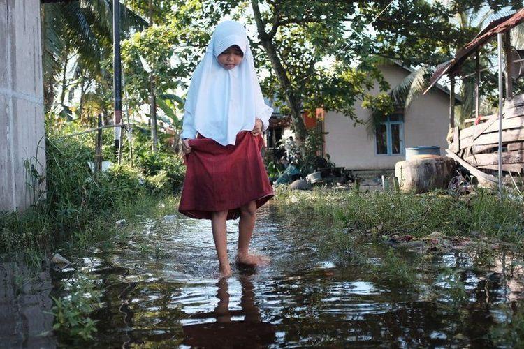 Seorang anak di Kubu Raya harus melalui genangan banjir rob demi menempuh pendidikan