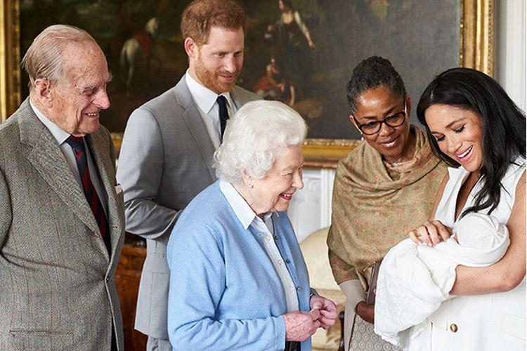 Pangeran Harry (dua kiri) dan istrinya, Meghan Markle (kanan) ditemani oleh ibu Meghan Doria Ragland, menunjukkan anak pertama mereka ke ke Ratu Inggris Elizabeth II (tengah) dan Pangeran Philip (kiri) di Windsor Castle, London, Rabu (8/5/2019) waktu setempat. Anak yang mereka beri nama Archie Harrison Mountbatten-Windsor itu berada di urutan ketujuh suksesi kerajaan Inggris.