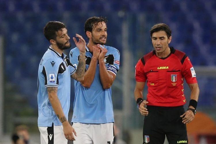 Pemain Lazio, Luis Alberto dan Marco Parolo, melancarkan protes kepada wasit Gianpaolo Calvarese dalam laga kontra AC Milan pada lanjutan pekan ke-30 Liga Italia yang digelar di Stadion Olimpico, Minggu (5/7/2020).