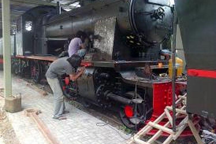 seorang pekerja tengah mengecat ulang salah satu lokomotif uap koleksi Museum Ambarawa, Rabu (28/1/2015) siang.