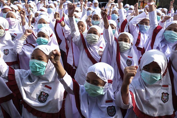 Siswa SD Islam Internasional Al-Abidin Solo memakai masker saat aksi peduli kesehatan bertajuk Waspada Virus Corona di halaman sekolah setempat, Solo, Jawa Tengah, Senin (3/2/2020). Aksi tersebut diisi dengan sosialisasi hidup sehat dan ajakan mendukung Warga China yang sedang menghadapi wabah Virus Corona untuk semangat.