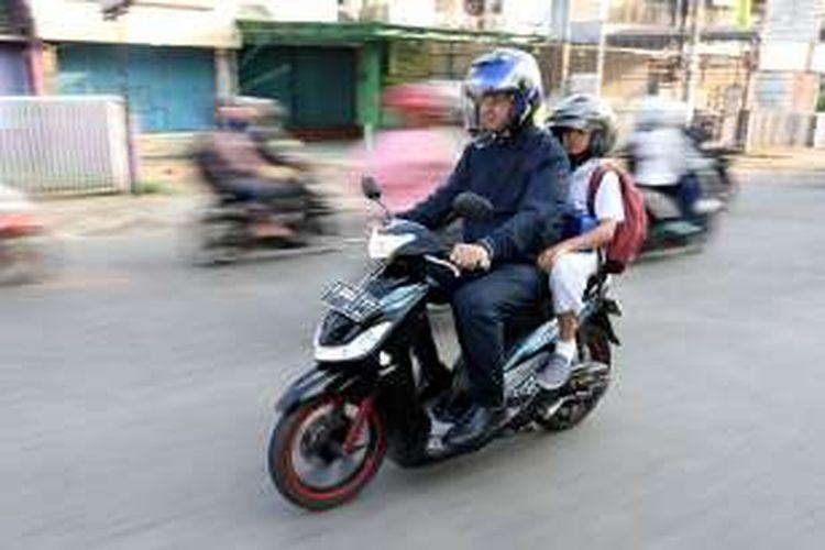 Mantan Menteri Pendidikan dan Kebudayaan Anies Baswedan mengantar putranya, Kaisar Hakam Baswedan, dengan sepeda motor pada hari pertama masuk sekolah di Cinere, Depok, Jawa Barat, Senin (1/8/2016). Saat menjabat menteri, Anies mengampanyekan Gerakan Antar Anak Ke Sekolah pada hari pertama masuk sekolah.