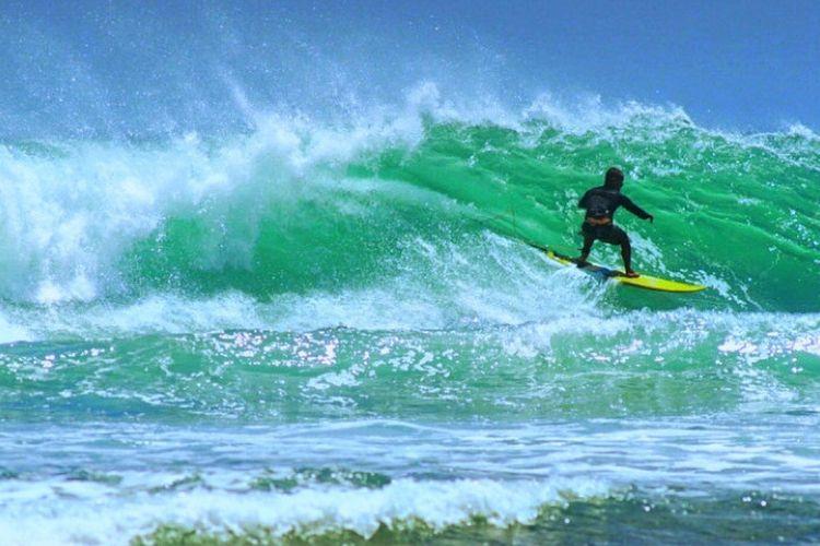 Wisatawan melakukan surfing di salah satu pantai di Bali.