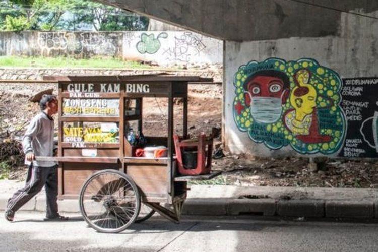 Pedagang kaki lima berjalan di dekat mural bertema pencegahaan penyebaran virus Corona atau COVID-19 di Jakarta, Rabu (01/04)