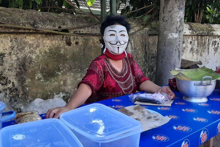 Nani Sugiarti (60) saat berjualan bubur dengan mengenakan topeng di jalan H. Agus Salim, Kota Yogyakarta.