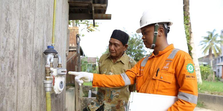 Petugas PT Perusahaan Gas Negara Tbk (PGN) sedang mengecek gas meter pelanggan jaringan gas rumah tangga.