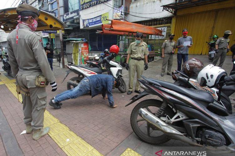 Petugas gabungan memberikan hukuman push up kepada warga yang tidak memakai masker saat razia penerapan aturan Pembatasan Sosial Berskala Besar (PSBB) di Kawasan Jalan Fatmawati, Jakarta, Selasa (28/4/2020). ANTARA FOTO/Reno Esnir/pras.