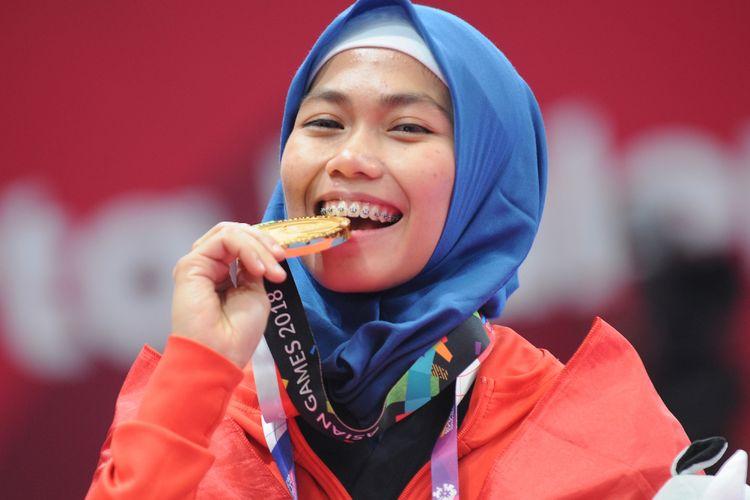 Taekwondoin putri Indonesia, Defia Rosmaniar menggigit medali emas yang diraihnya atas kemenangan di poomsae tunggal putri pertandingan Taekwondo di Asian Games 2018, di Jakarta Convention Center (JCC), Minggu (19/8). ANTARA FOTO/INASGOC/Sunyoto/inp/18