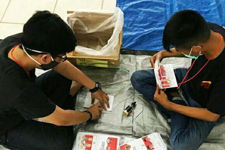 Dua petugas sortir dan pelipat surat suara untuk Pilkada Kalsel dan Pilkada Banjarmasin bekerja menyortir dan melipat surat suara di Gedung Wanita Banjarmasin.