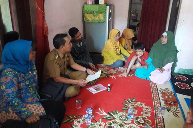 Sugiatmi (paling kanan), menceritakan meninggalnya anak bungsunya kepada petugas kesehatan yang datang berkunjung ke rumahnya, Senin (21/10/2019).