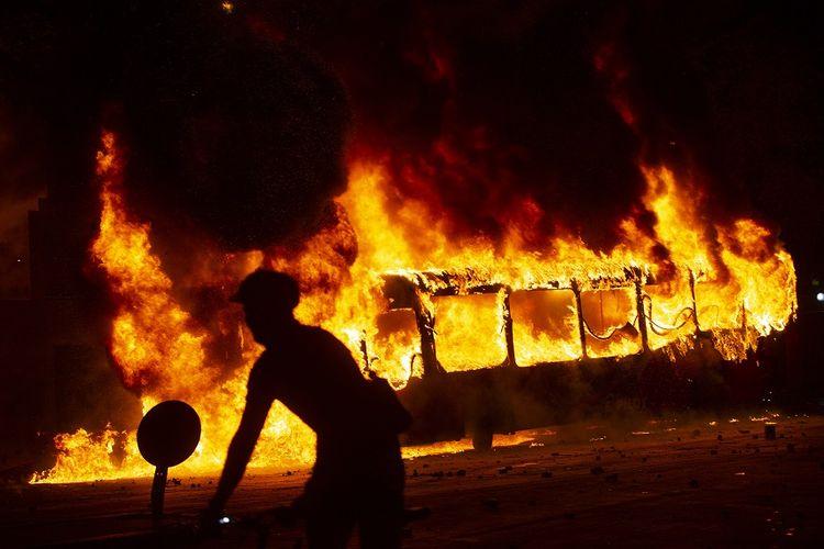 Seorang demonstran berjalan melewati sebuah bus yang terbakar di pusat kota Santiago, Chile, Jumat (18/10/2019), saat terjadinya unjuk rasa yang berakhir bentrok dalam protes kenaikan harga tiket kereta metro.