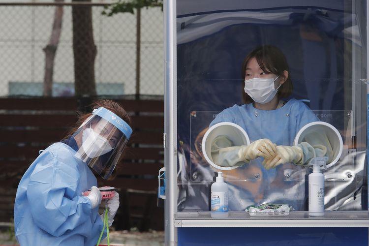 Seorang petugas medis membawa kipas angin portable untuk menyejukkan diri di tengah panasnya cuaca, saat melakukan tes Covid-19 ke para polisi di Kantor Polisi Metropolitan Seoul, Korea Selatan, pada Rabu (19/8/2020).