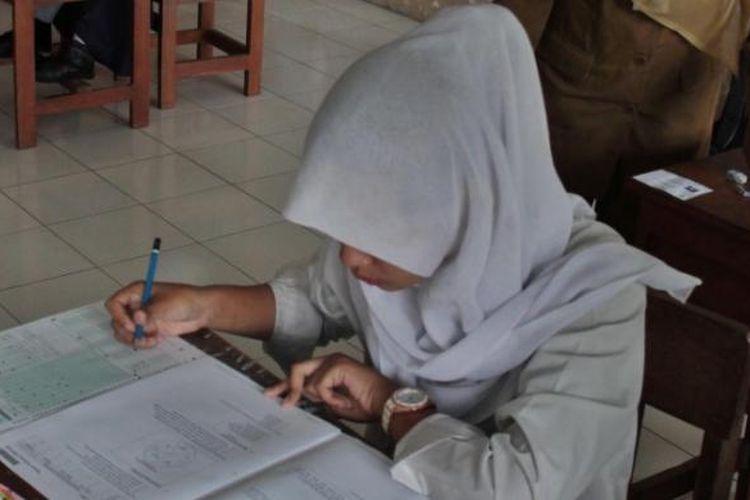 Seorang siswa SMPLB Muhammadiyah, Susukan, Kabupaten Semarang sedang mengikuti Ujian Nasional (UN) di SLB Negeri Ungaran, Senin (5/4/2015)