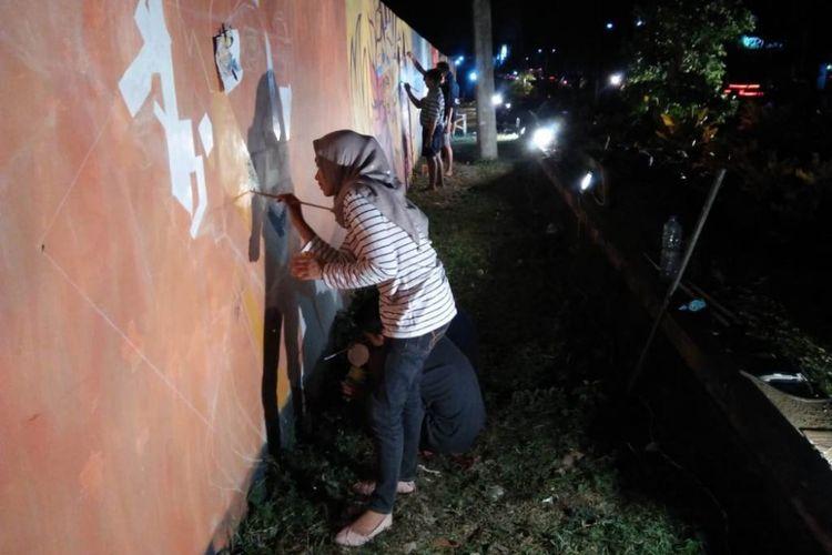 Sejumlah komunitas seni melukis di Trenggalek, Jawa Timur, melukis mural di tembok dinding kolam renang Tirta Jwalita (12/6/2018).