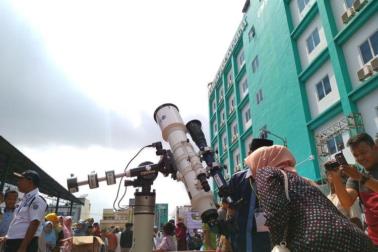 Seorang warga Medan melihat terjadinya gerhana matahari dengan teropong yang disediakan oleh Observatorium Ilmu Falak (OIF) UMSU, Kamis (26/12/2019).