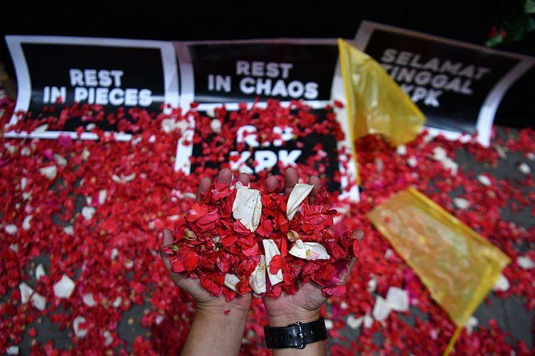 Warga yang tergabung dalam Koalisi Masyarakat Sipil Anti Korupsi menabur bunga di sekitar keranda hitam dan bendera kuning, di kantor KPK, Jakarta, Jumat (13/9/2019).Aksi tersebut sebagai wujud rasa berduka terhadap pihak-pihak yang diduga telah melemahkan KPK dengan terpilihnya pimpinan KPK yang baru serta revisi UU KPK.