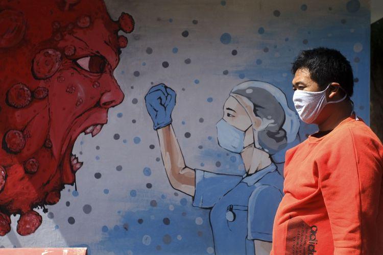 Warga melintas di dekat mural bergambar tenaga medis dan Virus Corona di kawasan Bantul, D.I Yogyakarta, Selasa (23/6/2020). Mural yang dibuat oleh warga itu guna mengingatkan warga agar waspada terhadap COVID-19 serta bertujuan untuk memberikan dukungan atas perjuangan tenaga medis yang menjadi garis terdepan dalam penanganan COVID-19. ANTARA FOTO/Andreas Fitri Atmoko/hp.