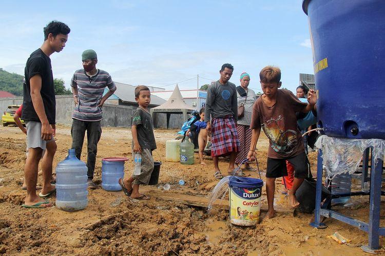 Sejumlah pengungsi antre mengambil air bersih di tempat pengungsian di Mamuju, Sulawesi Barat, Kamis (21/1/2021). Pasca Gempa bumi Sulawesi Barat berkekuatan Magnitudo 6,2 yang terjadi pada Jumat (15/1) lalu, kebutuhan air bersih di tempat tersebut masih tercukupi. ANTARA FOTO/ Akbar Tado/hp.
