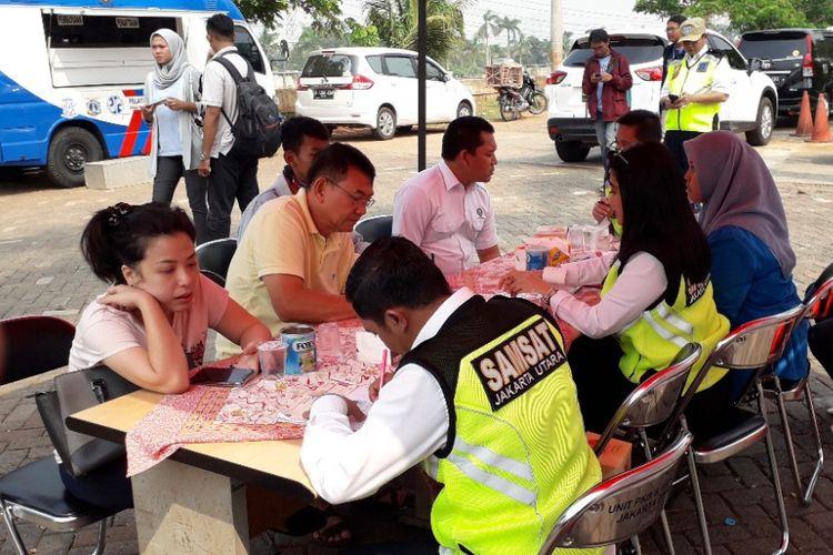 Sejumlah pelanggar razia pajak di Penjaringan mengurus pembayaran pajaknya di hadapan petugas Samsat Jakarta Utara, Rabu (21/11/2018).
