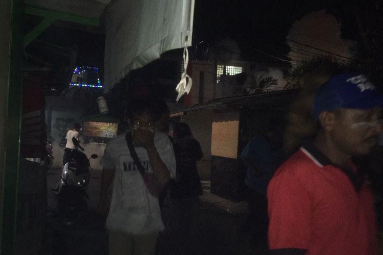Warga perkampungan yang tak sempat menjauh saat polisi yang tengah melakukan penyisiran peserta demo mahasiswa melontarkan gas air mata di depan Gedung II Kompas Gramedia, Jl Palmerah Selatan, Jakarta Pusat, Rabu (25/9/2019) dini hari.