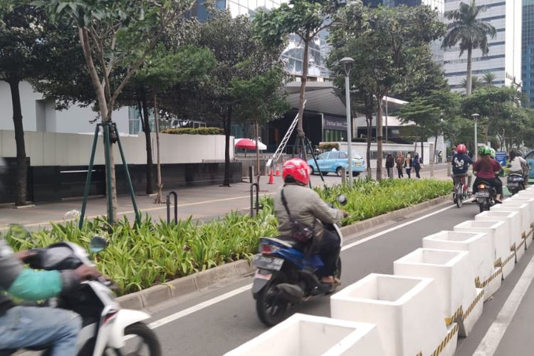 Jalur sepeda permanen di Jalan Sudirman Jakarta diserobot pengendara motor, Selasa (6/4/2021).