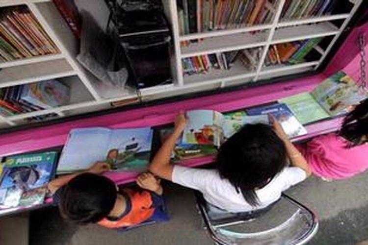 Anak-anak memanfaatkan mobil perpustakaan keliling untuk membaca di arena pameran perpustakaan yang diadakan untuk memperingati HUT Ke-33 Perpustakaan Nasional di Jakarta, Senin (13/5/2013). Pameran yang diikuti sejumlah perpustakaan dari berbagai instansi dan daerah ini untuk mengampanyekan minat baca di kalangan masyarakat. Pameran akan berlangsung hingga 17 Mei 2013.