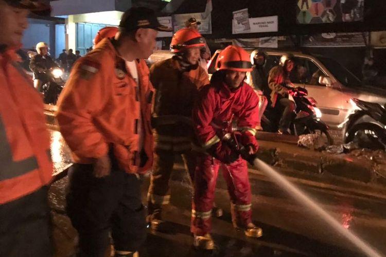 Petugas gabungan saling bahu membahu membersihkan lumpur di Jalan AH Nasution pasca banjir bandang yang terjadi Selasa (201/3/2018) sore.